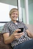 Envío de mensajes de texto de la edad adulta media alegre del hombre en el sofá en casa Fotos de archivo libres de regalías