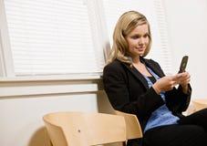 Envío de mensajes de texto de la empresaria en el teléfono celular Imagen de archivo libre de regalías