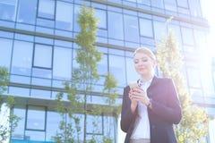 Envío de mensajes de texto de la empresaria a través del teléfono celular el día soleado Imagen de archivo libre de regalías