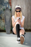 Envío de mensajes de texto de la muchacha del patinador Imagen de archivo libre de regalías