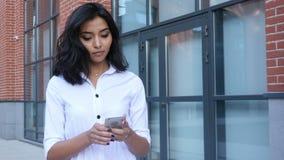 Envío de mensajes de texto de la muchacha en Smartphone y el caminar al aire libre almacen de metraje de vídeo