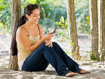 Envío de mensajes de texto de la mujer en el teléfono celular en la playa Imagenes de archivo