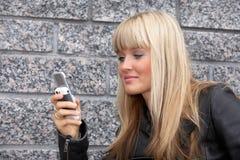 Envío de mensajes de texto de la mujer joven Imagenes de archivo