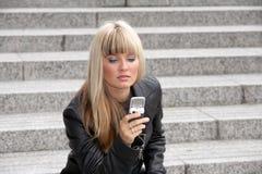 Envío de mensajes de texto de la mujer joven Imagen de archivo