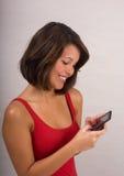 Envío de mensajes de texto de la mujer joven fotos de archivo libres de regalías