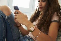 Envío de mensajes de texto del adolescente con el teléfono en casa, cerca para arriba Imagenes de archivo
