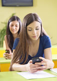 Envío de mensajes de texto del estudiante en el teléfono celular en sala de clase foto de archivo libre de regalías