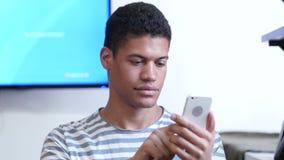 Envío de mensajes de texto en Smartphone del hombre negro almacen de video
