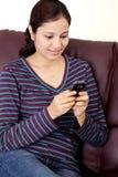 Envío de mensajes de texto feliz de la mujer joven Imágenes de archivo libres de regalías