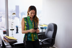 Envío de mensajes de texto hermoso de la mujer de Latina en el teléfono en oficina Fotografía de archivo