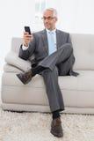 Envío de mensajes de texto maduro elegante del hombre de negocios en casa Foto de archivo