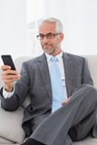 Envío de mensajes de texto maduro elegante del hombre de negocios en casa Fotos de archivo libres de regalías