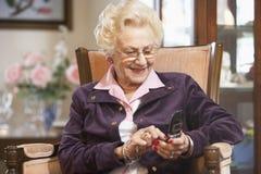 Envío de mensajes de texto mayor de la mujer Fotos de archivo