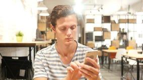 Envío de mensajes de texto ocupado creativo del hombre joven en Smatphone, retrato del texto que mecanografía almacen de metraje de vídeo