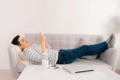 Envío de mensajes de texto del hombre en un teléfono móvil y sonrisa en casa imagenes de archivo
