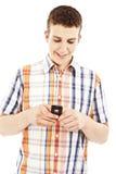 Envío joven del individuo sms con su teléfono móvil Fotos de archivo libres de regalías
