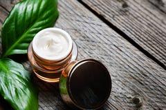 Envase cosmético con las hojas herbarias verdes, etiqueta en blanco de la botella para la maqueta de marcado en caliente, fotografía de archivo libre de regalías