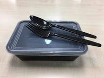Envase de comida plástico negro con la cuchara y la bifurcación Fotografía de archivo