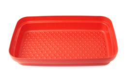 Envase de comida plástico rojo aislado sobre el fondo blanco Imágenes de archivo libres de regalías