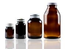 Envase de cristal ambarino de la botella de la droga con el casquillo cerrado aislado en el fondo blanco Diverso tamaño del envas imagen de archivo