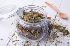 Envase de cristal con infusión de hierbas en la tabla blanca fotos de archivo