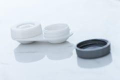 Envase de la lente de contacto, en el benchtop de mármol blanco foto de archivo libre de regalías
