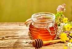 Envase de miel con el cazo con los wildflowers Fotografía de archivo