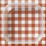 Envase de plástico sobre manteles rojos y blancos Imagen de archivo libre de regalías