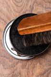 Envase de pulimento y de cepillo de zapato en de madera Fotografía de archivo libre de regalías