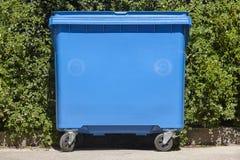 Envase de reciclaje azul para el papel con el fondo verde del arbusto Foto de archivo libre de regalías