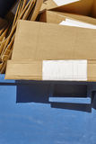 Envase de reciclaje azul para el papel con las cajas de cartón Fotos de archivo libres de regalías