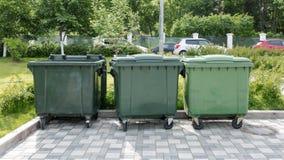 Envase de reciclaje plástico verde abierto en el stree soleado de la ciudad foto de archivo