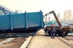 Envase del cargamento con la basura a una máquina especial para el transporte subsiguiente a una planta de eliminación de residuo Foto de archivo libre de regalías