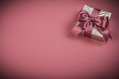 Envase del regalo con el arco atado en concepto rojo de los días de fiesta del fondo Imagen de archivo