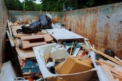 envase sobre los contenedores que fluyen que son llenos con basura Imagen de archivo libre de regalías