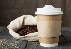 Envase-termos especiales para el café, bolso del paño con los granos de café en superficie de madera Imagenes de archivo