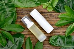 Envases cosméticos de la botella con las hojas herbarias verdes, paquete en blanco de la etiqueta para la maqueta de marcado en c imagenes de archivo