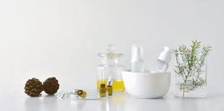 Envases cosméticos de la botella con las hojas herbarias verdes y la cristalería científica, paquete en blanco de la etiqueta par fotografía de archivo