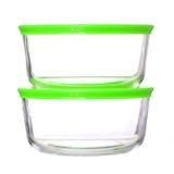 Envases de comida de cristal con las tapas plásticas verdes en blanco Fotos de archivo libres de regalías