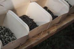 Envases de madera con las hojas de té foto de archivo