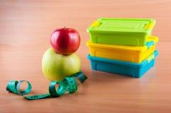 Envases de plástico coloridos que ponen en la tabla de madera cerca de manzanas y de la cinta métrica rojas, verdes Foto de archivo