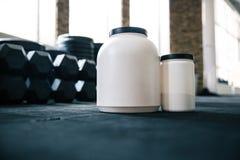 Envases de plástico con la nutrición de los deportes en pesas de gimnasia Imágenes de archivo libres de regalías