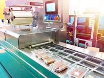 Envases de plástico con las salchichas en transportador en la fábrica de la comida imagenes de archivo