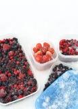 Envases de plástico de bayas mezcladas congeladas en nieve Imagen de archivo