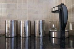 Envases del café, del azúcar y del té que descansan al lado de una caldera del wat Imagen de archivo
