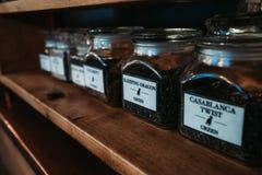 Envases del té en estante con el foco delantero fotos de archivo