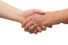 Envelhecimento - aperto de mão entre jovens e mulheres adultas Foto de Stock