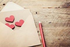 Envelop of brief en rode harten op rustieke lijst voor liefdebericht op Valentijnskaartendag in het retro stemmen stock foto's