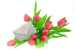 Envelop in een boeket van tulpen stock afbeelding