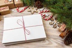Envelop met leeg blad van document op Kerstmisachtergrond - spartak, denneappels, rood lint, ster en hart van snoepjes Ruimtef stock afbeeldingen